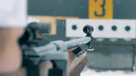 mass start : Snowfall and close up of rifles barrel during aiming process
