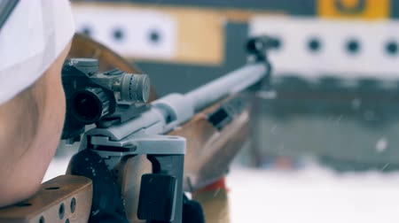 mass shooting : Female biathlete is preparing to shoot from a rifle Stock Footage
