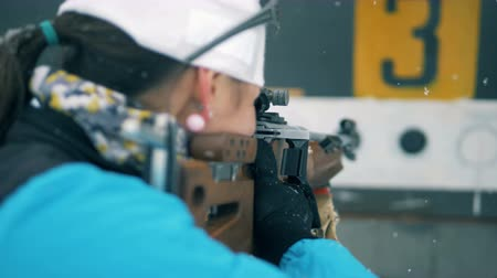 closing : Female biathlete is shooting and one target is being closed