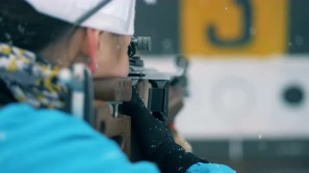 equipped : Backside view of a sportswoman shooting on a biathlon stadium Stock Footage