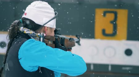 sztafeta : Lady athlete is shooting and targets are getting closed