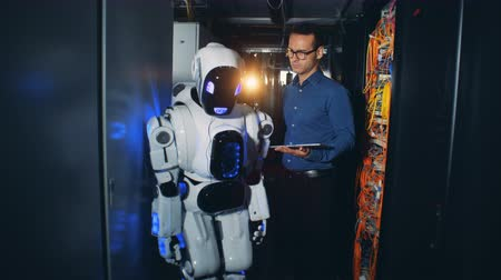 computer programmer : A man switch on a robot at a data center, close up. Stock Footage