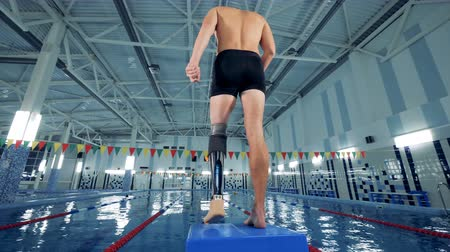 prosthesis : A man with a bionic leg is warming up in a swimming pool Stock Footage