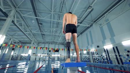 prosthesis : Swimming pool and a man with a robotic leg warming up