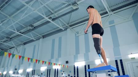 challenged : A male with a prosthetic leg is preparing to swim in a pool Stock Footage