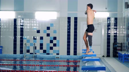 soutěže : A man with a bionic leg is stretching muscles to jump into the pool
