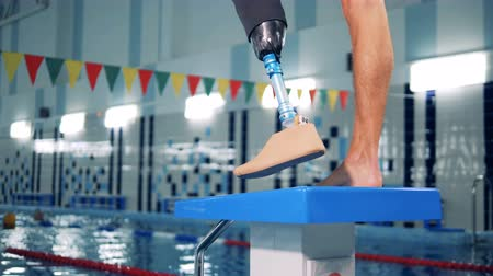 amputee : Close up of a male healthy leg and a prosthetic one in the swimming pool
