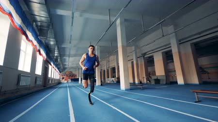 paralympics : A man is running along the gym with a prosthetic leg