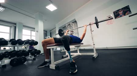 amputee : Gym room and a man with a robotic leg lifting a bar