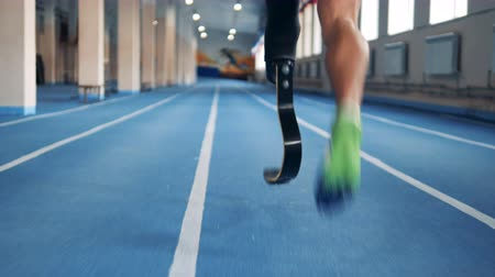 paralympics : Close up of a male prosthetic leg and a healthy one during jogging