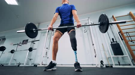paralympics : A man with a bionic leg starts lifting heavy weights in a gym