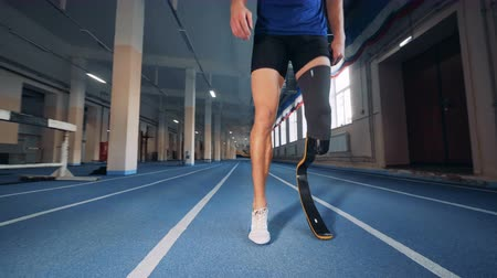 paralympics : Disabled man with a prosthetic leg is warming up before running