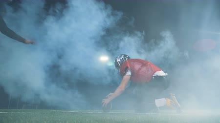 catch : Footballers playing on a smoked field, back view.
