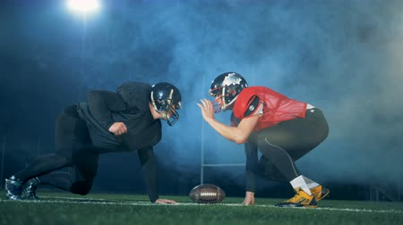 piłkarz : American football players standing in a pose near a ball, side view.