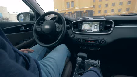 self driving : A car parking on autopilot while a man sits in it, close up.