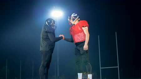 american football player : Football players shaking hands, side view.