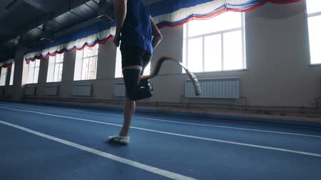 rehabilitasyon : One man running with prosthetic leg, side view. Stok Video