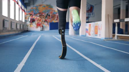 paralympic : Male sportsman running on a track, wearing prosthesis, back view.