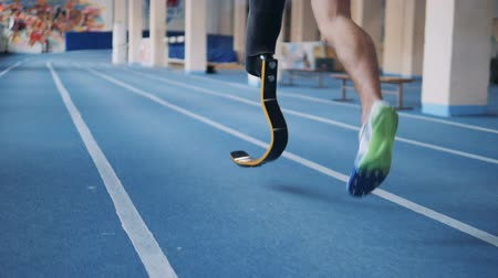 paralympics : One man with bionic leg training on a running track, back view. Stock Footage