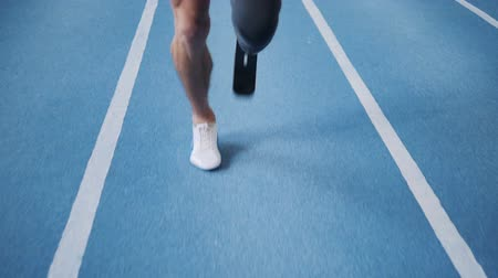 amputee : Man with leg prosthesis running on a training track, close up.