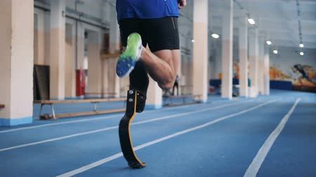 rehabilitasyon : Disabled runner with bionic prosthesis, back view. Stok Video