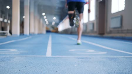 paralympic : Person with bionic prosthesis running on a special track, back view. Stock Footage