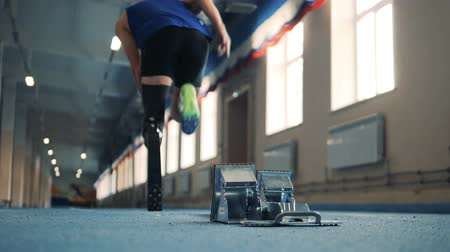 paralympic : Jogger starts to sprint, wearing bionic leg, back view.