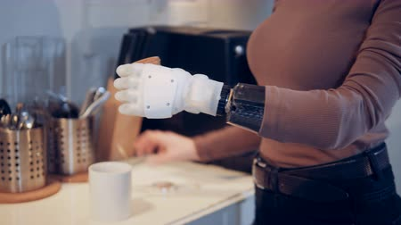 amputated : A lady with a bionic hand adds spice into the cup