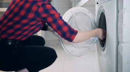substitute : Clothes is getting taken out from the washing machine by a lady with a bionic arm Stock Footage