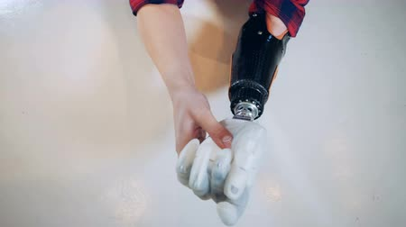 biophysics : Robotic hand is being assembled by a young female