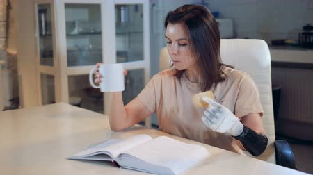 substitute : A lady with a prosthetic hand is drinking tea and reading a book