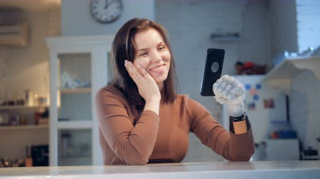 physically : Smiling lady with a prosthetic hand is having a videocall