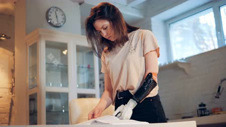 substitute : Books pages are getting turned by a young woman with a bionic arm Stock Footage
