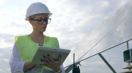 инспектор : Female engineer works with a tablet near solar panels, close up.
