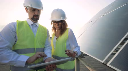 clean electricity production : A woman and a man work with a tablet near sun panels, close up.