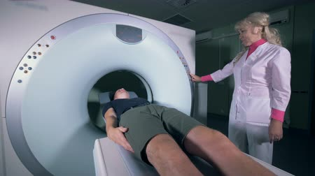 vacina : A doctor switches on a tomography machine, close up.