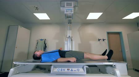 tomography : Man lying while tomographic machine scanning him, side view. Stock Footage