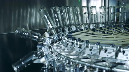 wódka : Glass bottles are getting lowered by a factory mechanism