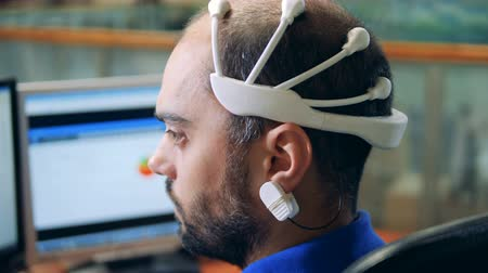 consciência : An engineer wearing special Brainwave Scanning sensors on a head, back view.