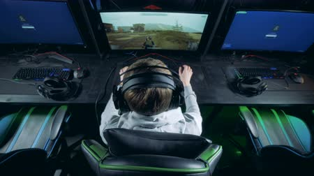 atirador : Young man is playing computer games with a headset on
