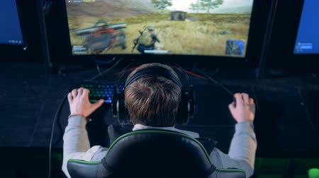 mmorpg : Young man is playing a videogame in a backside view Stock Footage