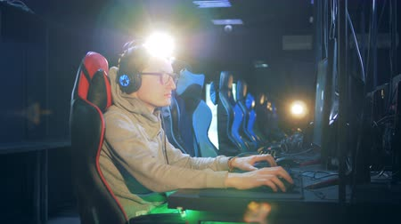 mmorpg : Young man in glasses and headphones is playing a computer game Stock Footage