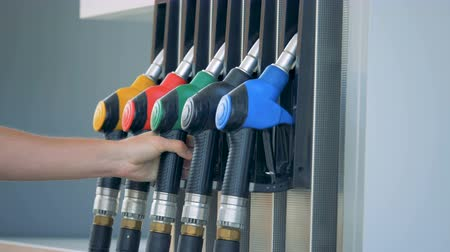 benzine : A person puts a gas nozzle back into the fuel pump Stock Footage