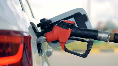 filling station : Side view of a petrol nozzle inserted into automobiles tank Stock Footage