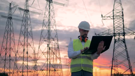 energetyka : Male technician is operating a laptop beside electrical transmission lines