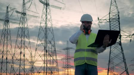 energetyka : Electrical transmission line and a male worker speaking on a phone