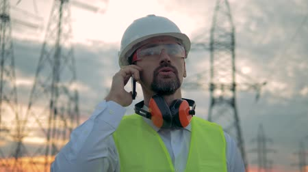 hardhat : Close up of a male engineers face while speaking on a phone near power lines