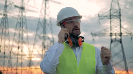 cabling : Phonecall of a male specialist standing beside electricity lines