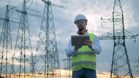 energetyka : Towers of power lines and a male technician operating a tablet