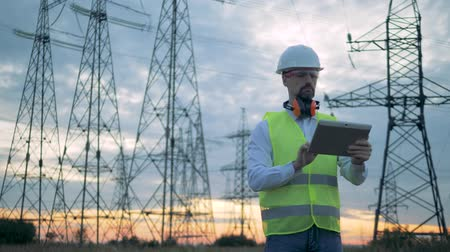 energetyka : Energetics employee is operating a tablet in front of electrical transmission lines
